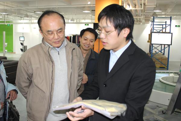 利奥创新科技工作人员向张建副局长介绍RFID智能标签在服装产业链上的应用优势